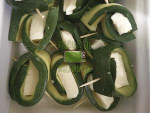 Tagliare la mozzarella a rettangoli, adagiarne uno sopra ogni zucchina e arrotolare in modo da ottenere degli involtini.